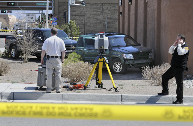 Police investigators work the area of a crime scene at the southeast corner of 57th street and Ouray Rd NW where a suspect, Mickey Owings crashed a green Jeep into a building following a police pursuit from the nearby Walmart department store parking lot, on March 29, 2010. (Pat Vasquez-Cunningham/Journal)