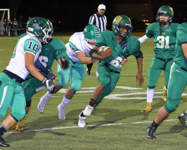 West Las Vegas star running back Darion Williams (with the ball) tries to elude the grasp of Pojoaque Valley's Jonathan Chavez in a game the Dons won 46-6 last week. (Courtesy of Shannon Steven Aragon)