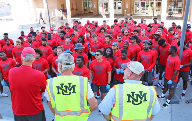 UNM football players, coaches help clean campus on day off
